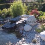 cascade d'eau qui glisse sur une pierre et qui tombe dans un bassin, jardin japonais, étang, plantations, ruissellement
